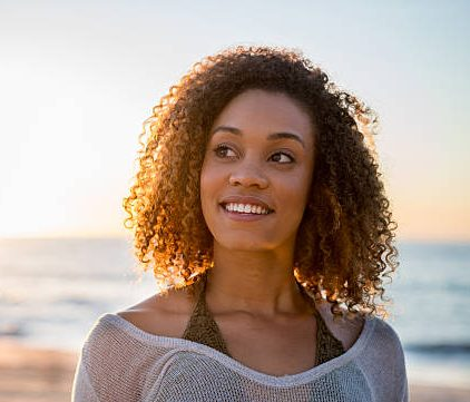 Portrait of a thoughtful black woman at the beach looking up and smiling